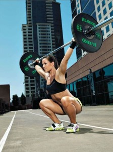A woman carrying a barbell while working out