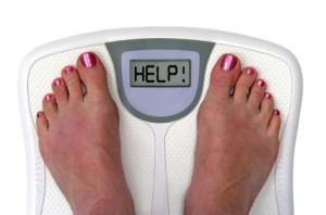Girl's feet on weighing scale saying HELP