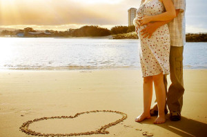 a couple expecting child standing on the beach