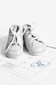 Baby's boots kept on top of a calendar maked due date