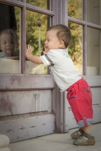 baby standing near window